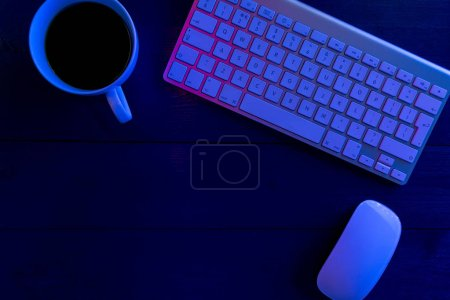 Cup of coffee and laptop keyboard on wooden office desk table at night with lights