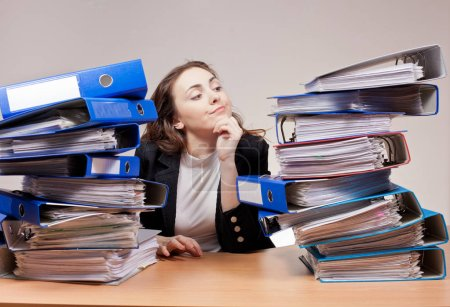 Photo pour Travail de bureau occupé. Femme d'affaires bouleversée avec pile de dossiers et de documents au bureau - image libre de droit