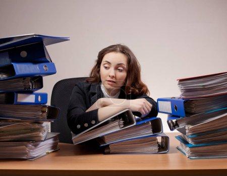 Photo pour Gestionnaire de l'occupé. Femme d'affaires frustré avec pile de dossiers et de documents - image libre de droit
