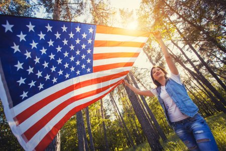 happy smiling young woman with national american flag outdoors. Independence Day, 4th July
