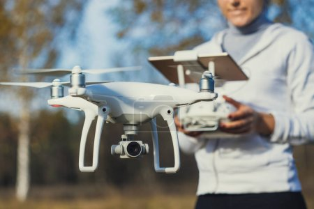 Photo for Man controls quadrocopter flight. Flying the copter. Remote control in a women's hands - Royalty Free Image