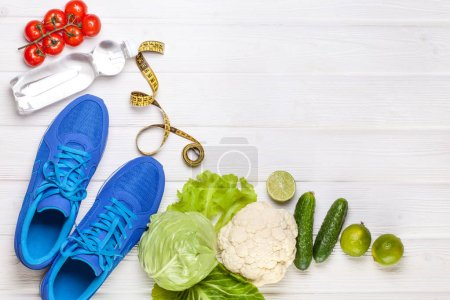 Photo for Fitness, active lifestyles Concept. Fresh healthy vegetables, sport shoes on white wood background. copy space for text. Top view - Royalty Free Image