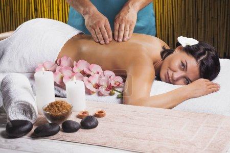 Photo pour Belle brune dans un salon de massage. spa avec bougies et orchidées - image libre de droit