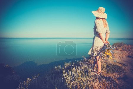Photo for Beautiful young woman in a hat on a high sea cliff with a bouquet of flowers in a retro hat. - Royalty Free Image