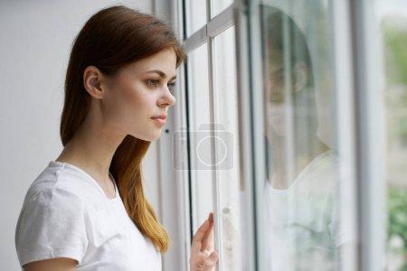 Photo pour Vue latérale d'une jolie jeune femme regardant par la fenêtre dans la chambre - image libre de droit