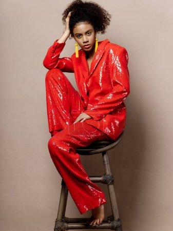 Photo pour Femme en costume rouge paillettes boucles d'oreilles jaunes fête disco - image libre de droit