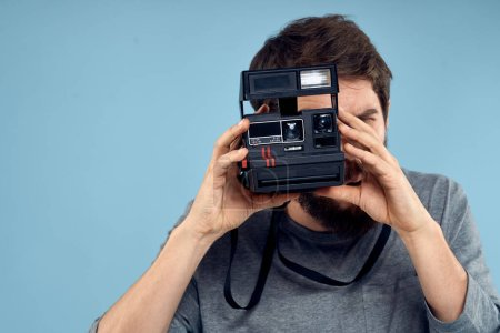 Photo for Male photographer with a professional camera in his hands near the face of a hobby Creative approach blue background. High quality photo - Royalty Free Image