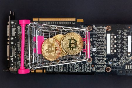 Stack of coins bitcoin in mini shopping cart toy on the video card, concept of mining. Electronic virtual money for web banking and international network payment. Symbol of crypto currency