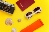 Flat Lay with sunscreen, vintage camera, passport, sunglasses and shell on yellow colourful trendy modern fashion background. Vacation travel summer weekend sea adventure trip concept