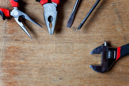 Variety of repair tools: pliers, screwdriver, adjustable wrench on old rustic wooden background and place for text copyspace