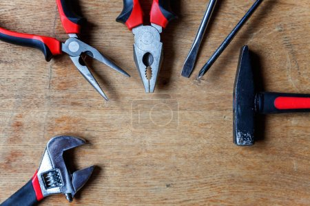 Variety of repair tools: pliers, screwdriver, hammer, adjustable wrench on old rustic wooden background and place for text copyspace