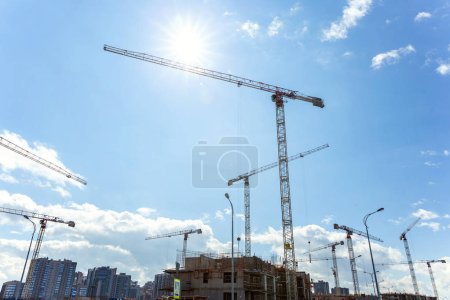 Cranes at construction site against blue sky