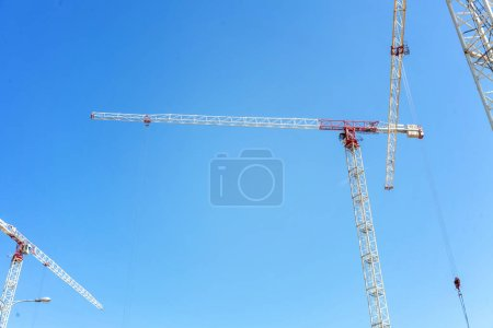 Cranes and workers at construction site against blue sky