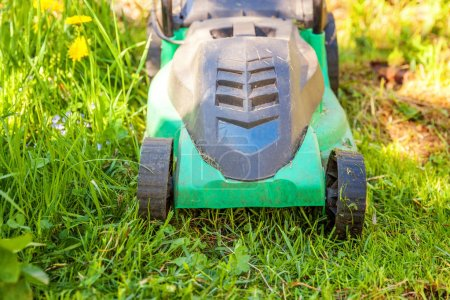 Lawn mower cutting green grass in backyard in sunny day. Gardening country lifestyle background. Beautiful view on fresh green grass lawn in sunlight, garden landscape in spring or summer season