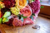"""Постер, картина, фотообои """"Красивые свадебные кольца лежат на столе на фоне букет цветов"""""""