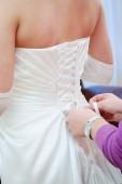 Bridesmaid helping bride with her wedding dress. Wedding details