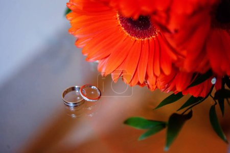 Beautiful wedding rings lie on a table against the background of a bouquet of orange gerbera