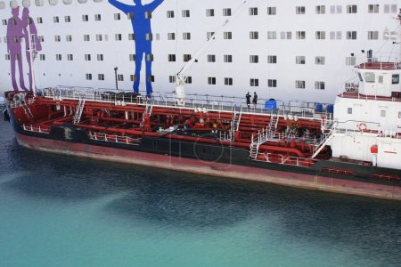 Delivering ship refueling big white passenger cruise liner. Refueling of heavy commercial ship in water at harbor.
