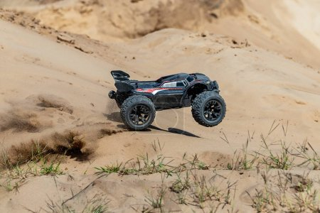 Big radio controlled buggy car driving fast and slipping on sand. RC toy moving fast on cross-terrain surface with dust and mud outdoors. Children hobby concept