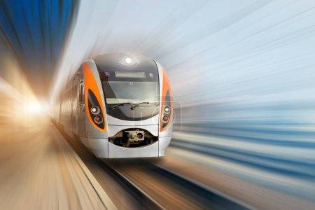 Moderne à grande vitesse électrique train de voyageurs se déplaçant rapidement le long de la plate-forme terminal. Flou de mouvement