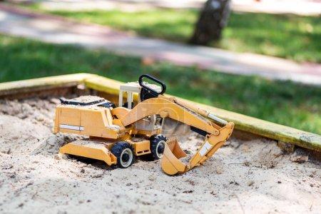 Juguete de excavadora amarillo en caja de arena de madera en el patio. concepto de juguetes para niños