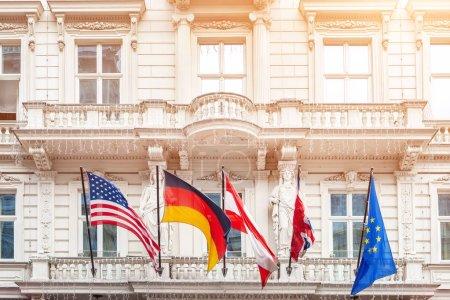 Photo pour Drapeaux nationaux sur l'ancienne façade de l'édifice dans la ville européenne. Le drapeau drapeaux des Usa, Allemagne, Autriche, Union européenne et plié la Grande-Bretagne. Brexit concept. - image libre de droit