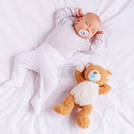 high angle view of adorable little boy with baby dummy sleeping with teddy bear