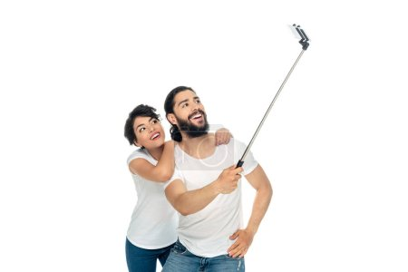 Photo for Cheerful latin man smiling near brunette woman while holding selfie stick and taking selfie isolated on white - Royalty Free Image