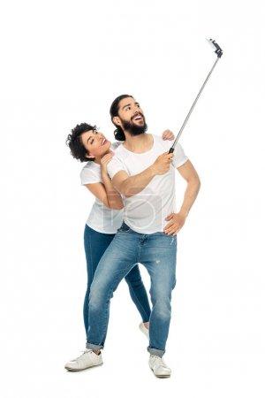 Photo pour Homme latin heureux souriant près de la femme brune tout en retenant le bâton de selfie et en prenant le selfie d'isolement sur le blanc - image libre de droit
