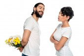 cheerful latin man holding yellow flowers near woman standing with crossed arms isolated on white