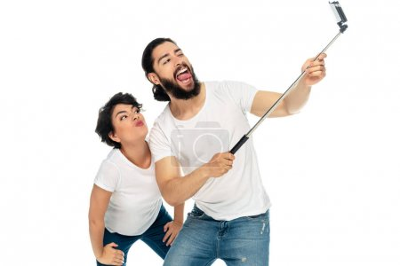 Photo for Happy latin man showing tongue near brunette woman and holding selfie stick while taking selfie isolated on white - Royalty Free Image