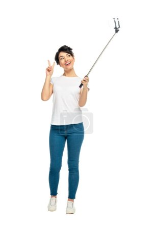 Photo pour Cheerful latin woman showing peace sign while holding selfie stick and taking selfie isolated on white - image libre de droit