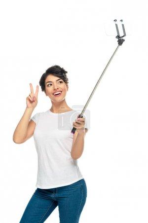 Photo pour Femme latine heureuse affichant le signe de paix tout en retenant le bâton de selfie et prenant le selfie d'isolement sur le blanc - image libre de droit