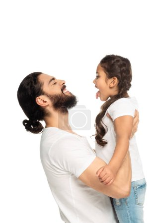 Photo pour Happy latin father smiling while holding in arms cute daughter showing tongue isolated on white - image libre de droit