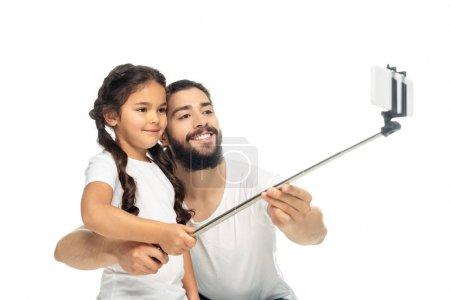 Foto de Niño feliz sosteniendo palo selfie mientras toma selfie con el padre latino aislado en blanco - Imagen libre de derechos