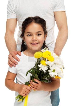 Photo pour Vue recadrée de père restant près de la fille latine avec des fleurs jaunes d'isolement sur le blanc - image libre de droit