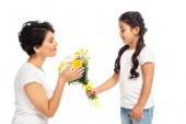 happy kid giving flowers to attractive latin mother isolated on white