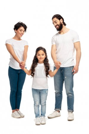 Foto de Happy latin parents holding hands with cute daughter while standing isolated on white - Imagen libre de derechos