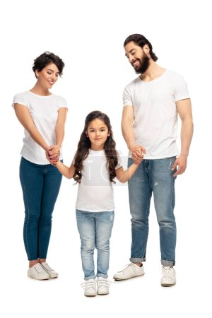 Photo pour Happy latin parents holding hands with cute daughter while standing isolated on white - image libre de droit