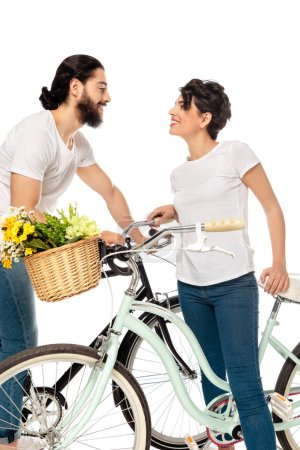Photo for Happy latin man looking at attractive brunette woman while standing near bicycle isolated on white - Royalty Free Image
