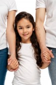 cropped view of parents holding hands with cheerful latin daughter while standing isolated on white