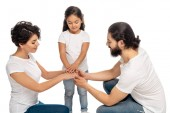 happy latin parents putting hands together with cute daughter isolated on white