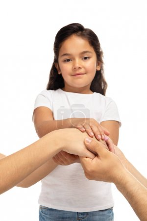 Foto de Cropped view of parents putting hands together with latin daughter isolated on white - Imagen libre de derechos