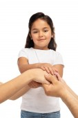 cropped view of parents putting hands together with latin daughter isolated on white