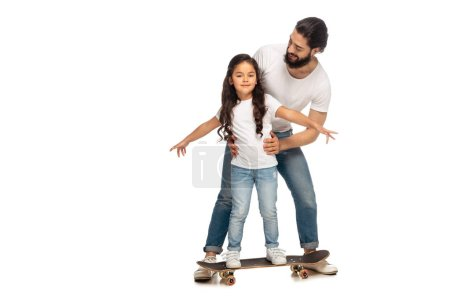 Photo for Happy latin father looking at cute daughter riding penny board isolated on white - Royalty Free Image
