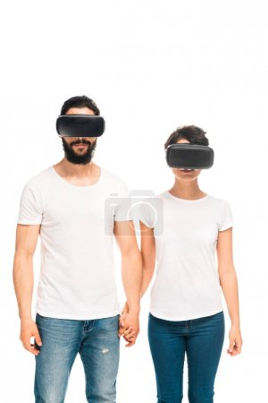 Photo for Latin man and woman wearing virtual reality headsets and holding hands while standing isolated on white - Royalty Free Image