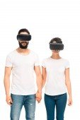 latin man and woman wearing virtual reality headsets and holding hands while standing isolated on white