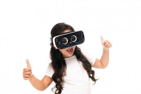 Photo pour Enfant latin affichant des pouces vers le haut tout en portant le casque de réalité virtuelle isolé sur le blanc - image libre de droit