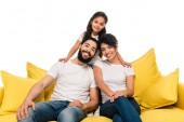 cheerful latin parents smiling while sitting on sofa near daughter isolated on white
