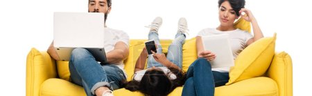 panoramic shot of kid lying on sofa and holding smartphone with blank screen near latin parents using gadgets isolated on white